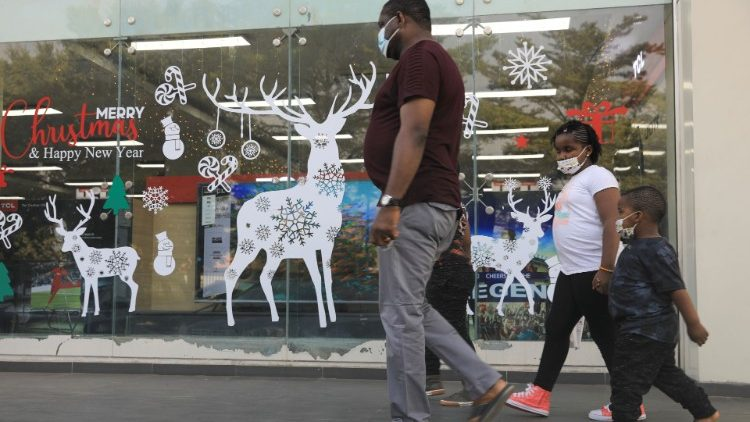 A family walk past Christmas decorations at Cherries Hypermarket on the eve of Christmas during the coronavirus disease (COVID-19) outbreak in Abuja