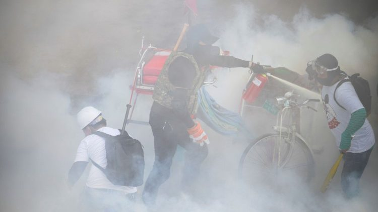 Tear gas floats around demonstrators at a protest in Yangon