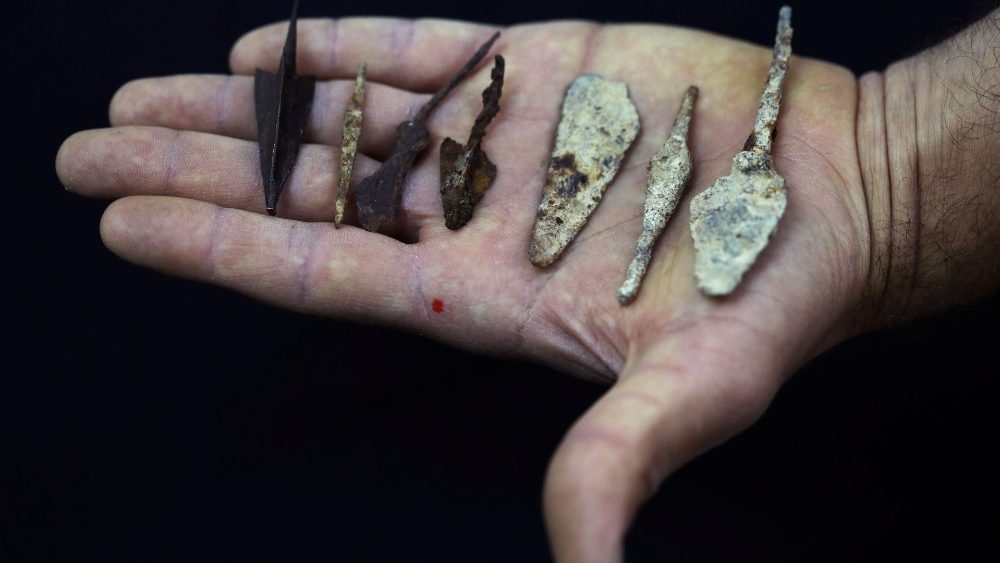 An employee holds ancient arrow and spear heads, part of various artefacts recently discovered in the Judean Desert caves along with scroll fragments of an ancient biblical texts, during an event at Israel Antiquities Authority laboratories in Jerusalem
