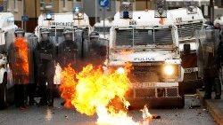 A fire burns in front of police in Belfast, Northern Ireland, on 8 April