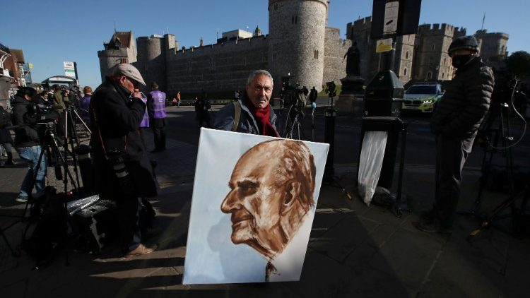 A man holds a painting of Prince Philip outside Windsor castle