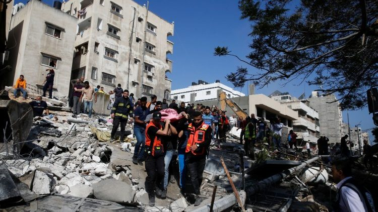 Rescue workers assist victims amid the rubble left by an Israeli air strike on Gaza City
