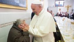 Pope Francis shares a meal with poor people at a soup kitchen