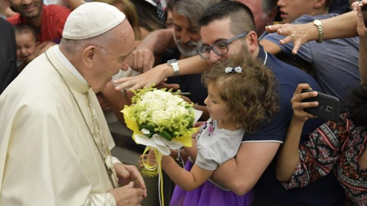 Pope Francis greets a child at the General Audience