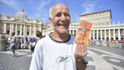 A man holds his crucifix distributed at the Sunday Angelus