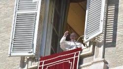 Pope Francis waves to pilgrimis present at the Angelus prayer