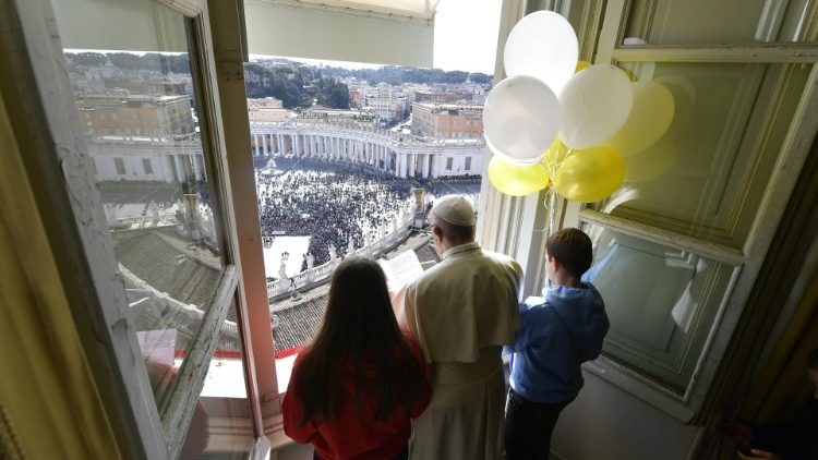 Pope Francis is accompanied at the Angelus by two children holding balloons