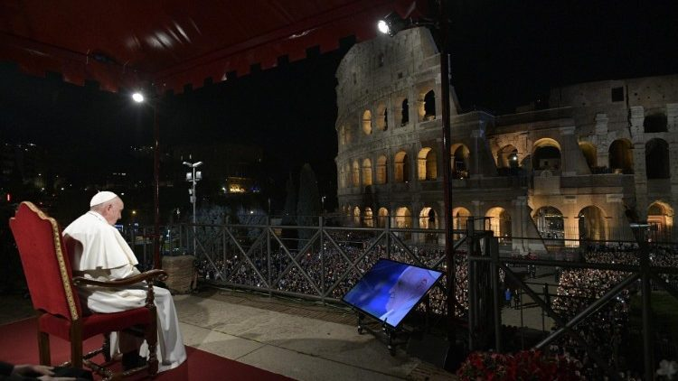 Pope Francis sits in front of the Colosseum