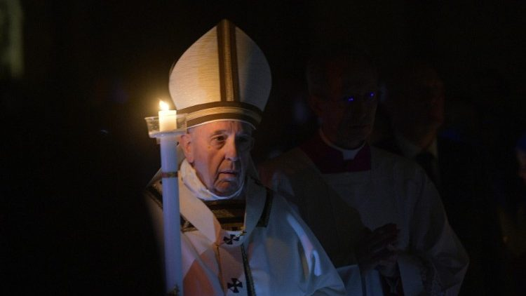 Pope Francis carries a lighted candle at the Easter Vigil