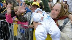 An elderly woman holds her grandchild up for Pope Francis in Romania