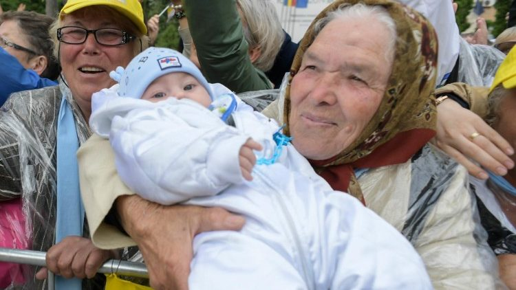 A grandmother proudly holds up her grandchild for Pope Francis in Romania