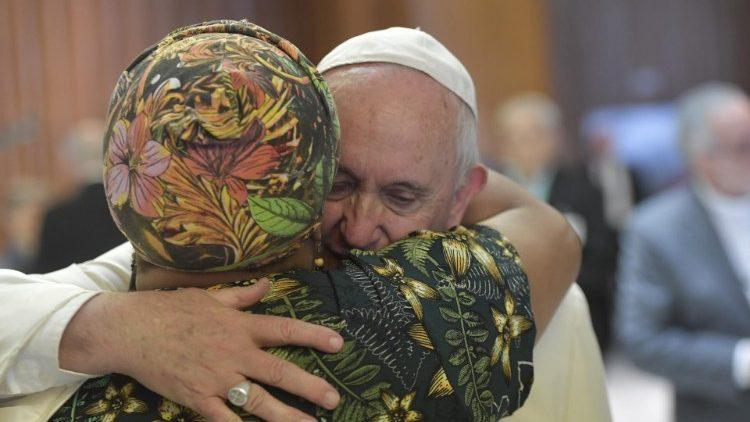 a abraza a una participante durante la Tercera Congregación General del Sinodo para la Amazonía.