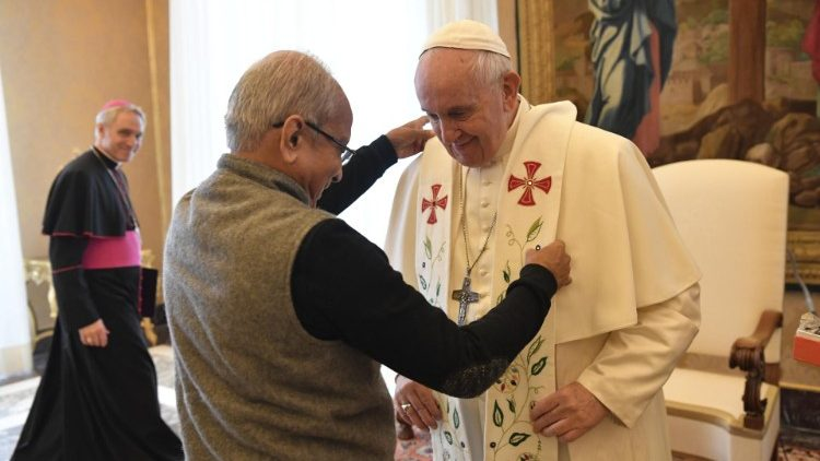 Father Cedric Prakash puts the stole on Pope Francis's shoulders during a papal audience