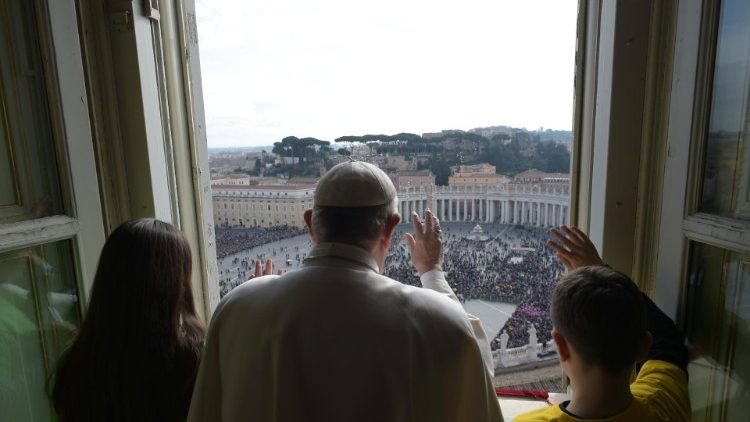 Pope Francis greets the crowds from the balcony overlooking St. Peter's Square
