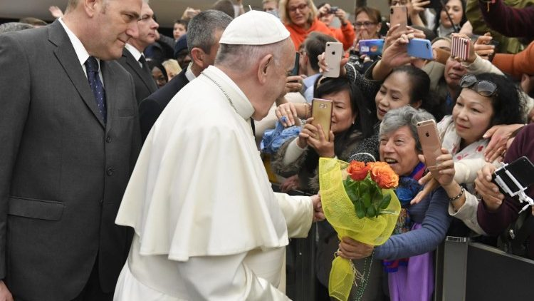 A woman gives Pope Francis a bouquet of flowers at the General Audience