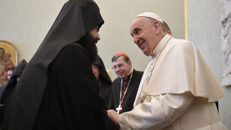 Pope Francis shakes hands with a member of the Orthodox delegation