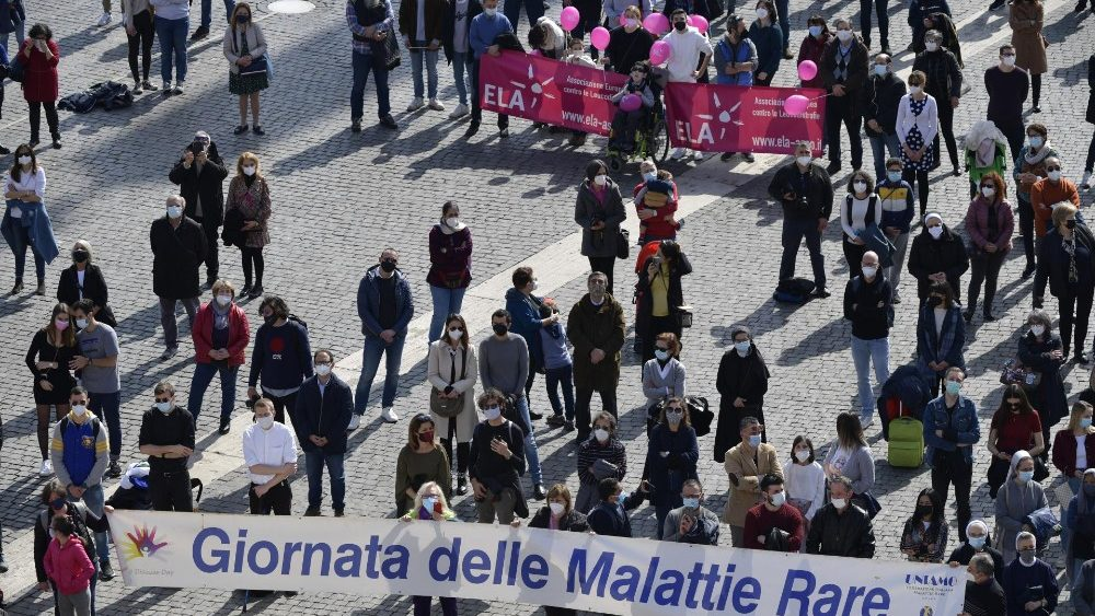 """Members of a solidarity association in St. Peter's Square hold a banner reading: """"World Rare Diseases Day"""""""