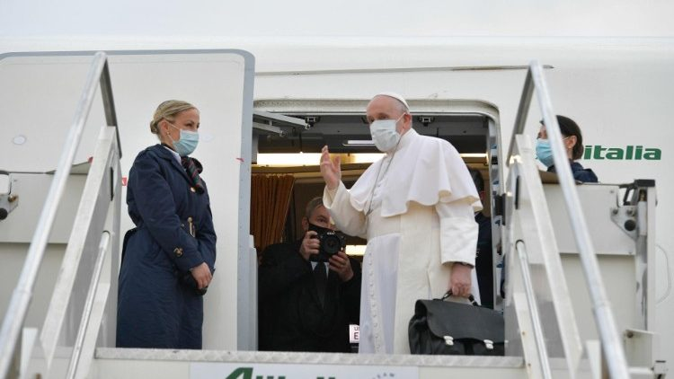 Pope Francis waves as he boards the papal plane