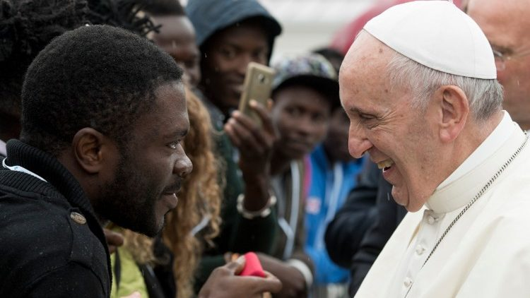 Pope Francis greets a migrant at Rome's Centro Astalli