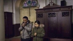 Chinese Catholics pray during Mass in Beijing