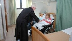 A member of the Brothers Hospitallers of Saint John of God cares for a patient