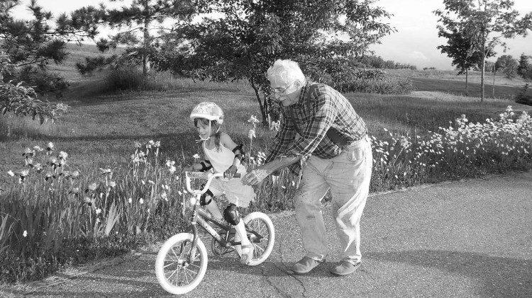 Un grand-père apprenant à sa petite-fille à faire du vélo.