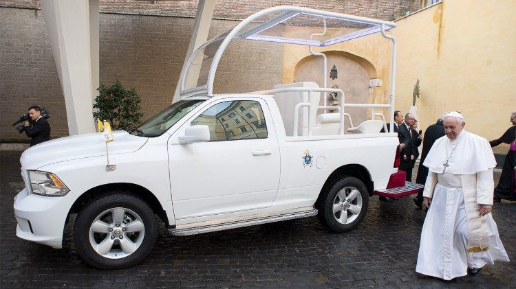 Pope Francis walking by donated Popemobile.