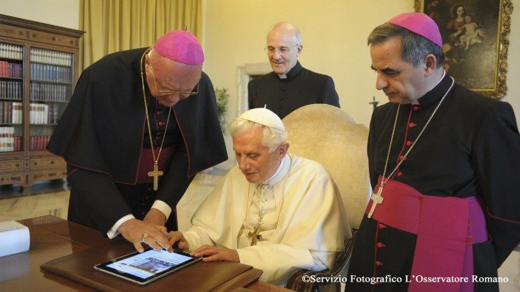 Pope Benedict XVI posts the first papal Tweet, flanked by Archbishop Angelo Becciu (R) on 12 Dec 2012