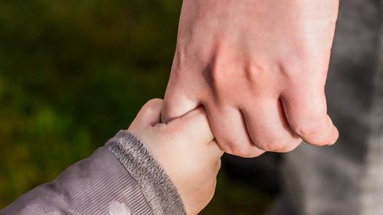 Mãos de criança e adulto