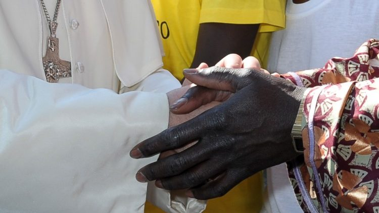 Pope Francis greeting a migrant on his first visit to the island of Lampedusa