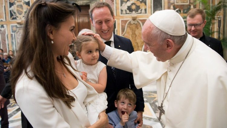 Pope Francis greeting mother and her little girl.