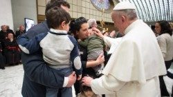 Pope Francis meeting a family in the Vatican.