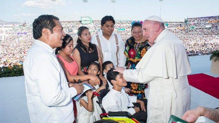 Pope Francis speaks to a family