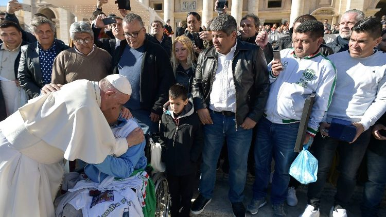 Pope Francis blessing a sick person.