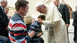 Pope Francis embraces a child