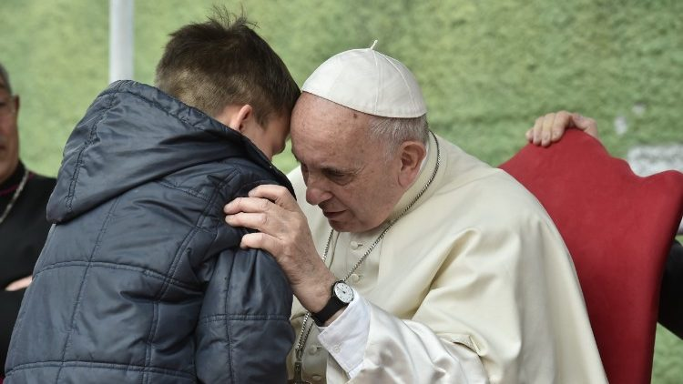 Pope Francis listens to a young boy during his parish visit on Sunday