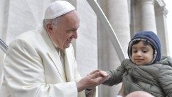 Pope Francis takes the hand of a child at his general audience.