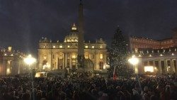 View of St Peter's Square with Nativity scene and Christmas tree in the foreground.