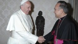 Archbishop Edgar Peña Parra shakes hands with Pope Francis