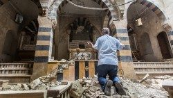 A man prays in a destroyed church