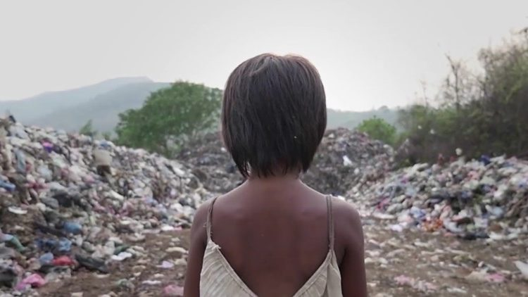 A little girl walks amid mountains of trash