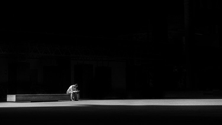 A man sits alone in darkness