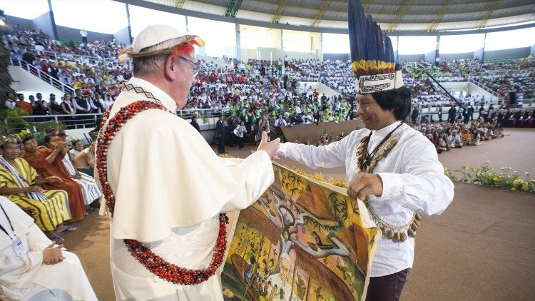 Pope Francis accepts a gift from a person from the Amazon region