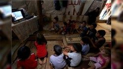 Displaced children watch SAT-7 satellite TV in a tent in a refugee camp