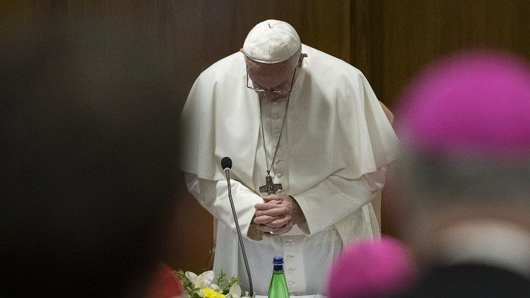 Pope Francis bows his head in prayer