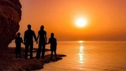 A family observes an ocean sunset