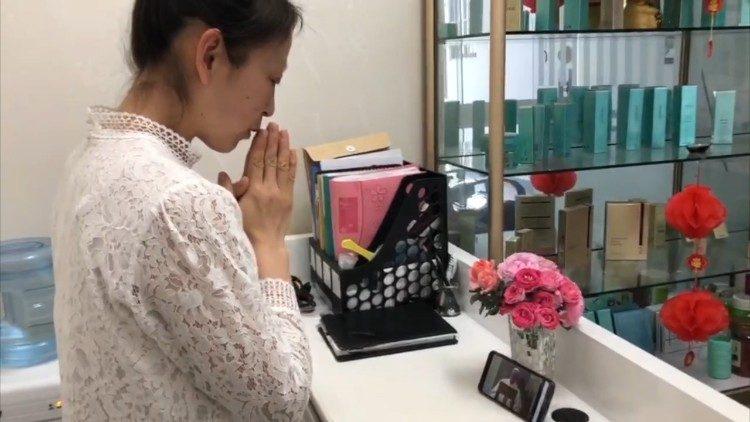 Une fidèle chinoise suit la messe du Pape à Sainte-Marthe