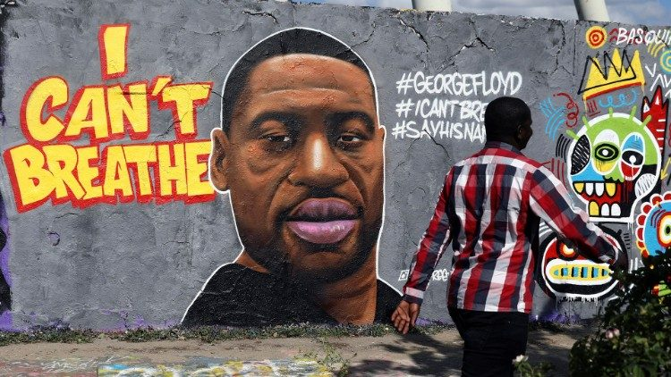 A man walks in front of a mural in honor of George Floyd