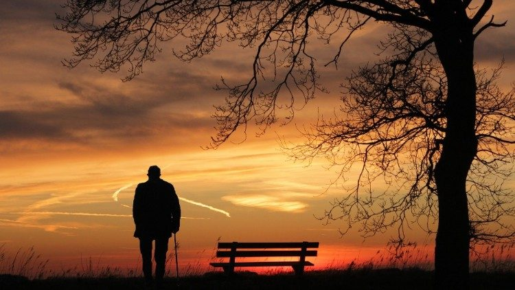 An elderly person gazes upon a sunset
