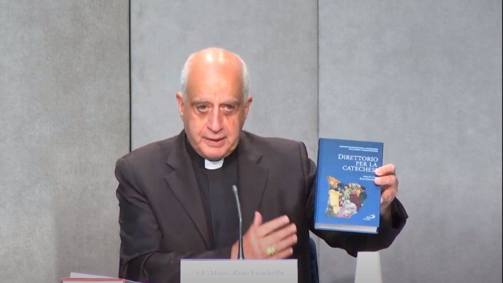 Monsignor Fisichella con una copia del nuovo Direttorio per la catechesi